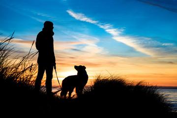 Silhouette von einem Mann und einen Hund am Strand bei Sonnenuntergang umrahmt von Gräsern