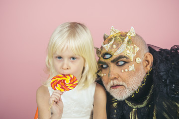Innocent child with colorful lollipop embraced by old monster with thorns, warts and dragon skin. Lovely blond girl with male demon isolated on pink background. Fantasy world, good and evil concept.