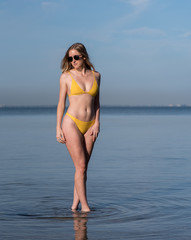 Portrait of a attractive woman in a yellow bikini and sunglasses standing in the water