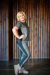 Beautiful blonde woman in jeans, t-shirt and winter boots stands, on a brown wall background