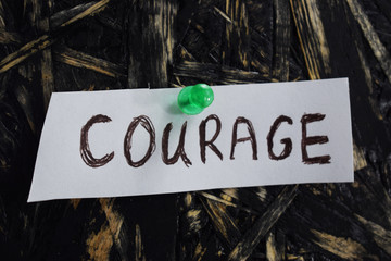 written courage on a white sheet of paper