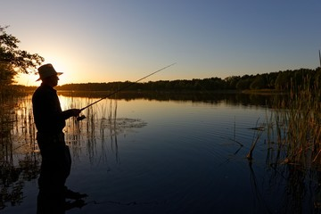 Silhouette of fisherman standing in the lake and catching the fish during sunset