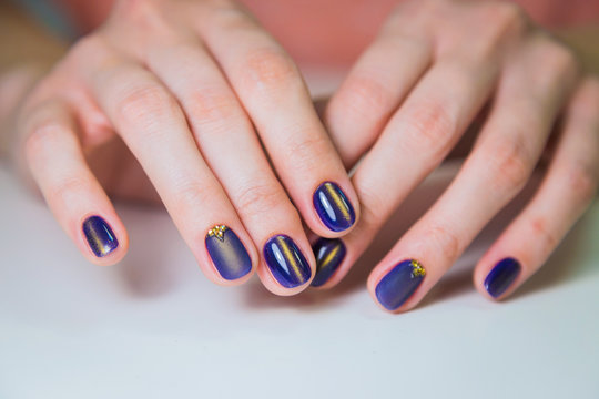 Finished purple shellac manicure, woman in nail beauty salon. Hands lie on white table and show the beautiful manicure