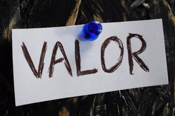 valor written in Spanish, means to courage , on a white sheet of paper.