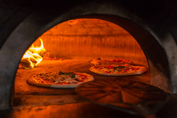 Fototapeta Original neapolitan pizza margherita in a traditional wood oven in Naples restaurant, Italy