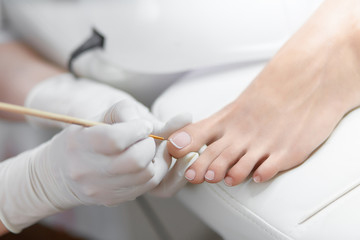 La pose en embrasure Pedicure Specialist in beauty salon making french pedicure for female client.