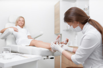 Podiatrist female doctor making procedure of massage and peeling.