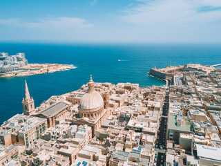 Aerial drone sunset photo over Our Lady of Mount Carmel basilica. A domed cathedral that overlooks the ancient capital city of Valletta, Malta. Island country in the Mediterranean Sea.