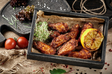 Wooden tray with fried chicken legs in a barbecue, lemon and tomatoes.