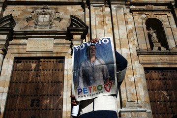 """A supporter of the Colombian presidential candidate Gustavo Petro holds a sign that reads """"I vote Petro"""" during a campaign rally in front of the Primatial Cathedral of Bogata on Bolivar square at La Candelaria in Bogota, Colombia"""