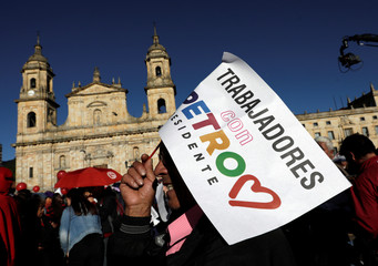 """A supporter of the Colombian presidential candidate Gustavo Petro holds a sign that reads """"Workers with Petro"""" during a campaign rally in front of the Primatial Cathedral of Bogota on Bolivar square at La Candelaria in Bogota"""
