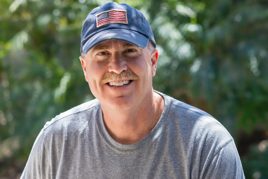 Smiling senior male wearing USA patriotic baseball hat in natural light