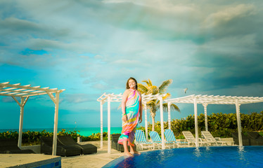 happy joyful, smile little girl standing on the edge of swimming pool near the beach area and looking aside on dark dramatic sky background with sun rays coming from the clouds