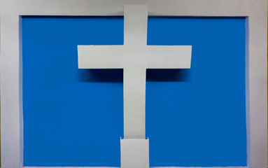 cruz blanca que sobresale de la pared, con un fondo azul