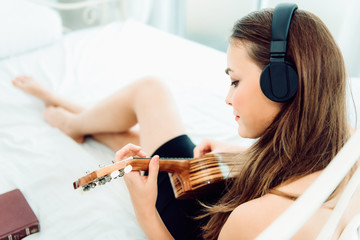 Portrait of young caucasian woman sitting on her bed and playing guitar relaxing with headphones, Leisure activities concept