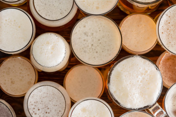 Multiple full, frothy beer glasses and sizes