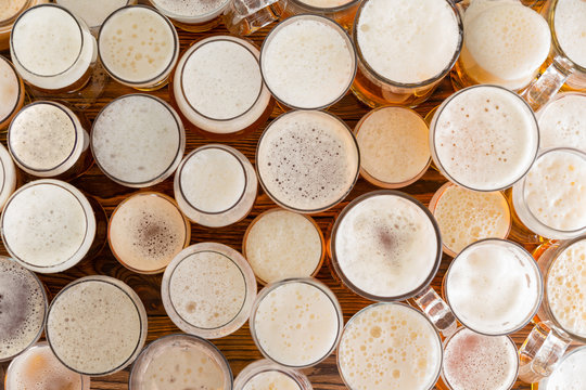 Assortment of full, frothy beer glasses and sizes