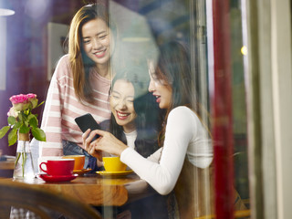 three young asian women looking at mobile phone in coffee shop