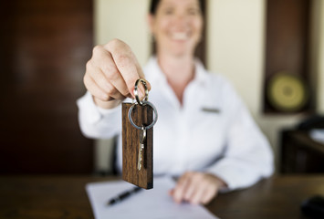 Receptionist handing room key to guest