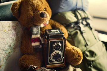 Closeup of a teddy bear with a camera and a map