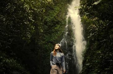 Asian woman enjoying a waterfall