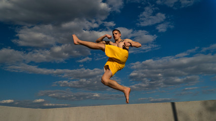 Tricking on street. Martial arts. Man is making high jab in jump barefoot. Shooted from bottom foreshortening against sky.