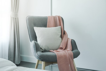 Pink scarf and beige pillow on gray armchair at the corner of living room