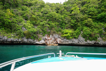 speed boat and green rock mountain
