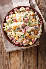 Hawaiian food: salad with pasta, ham, pineapple, onion, cheddar cheese with mayonnaise close-up in a bowl. Vertical top view