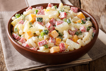 Hawaiian cuisine: salad with pasta, ham, pineapple, onion, cheddar cheese with mayonnaise close-up. horizontal, rustic style