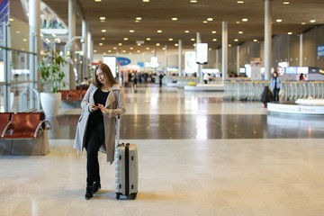 Nice female person going in airport waiting room with valise and using smartphone. Concept of traveling abroad and communication by mobile phone, free hotspot.