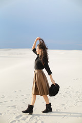 Caucasian fashionable female photo model standing on snow and wearing skirt and black blouse, keeping hat. Concept of fashion and vogue, monophonic background.