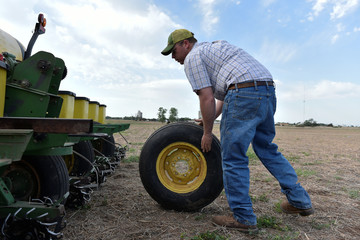 Cotton Farmer Drew Malchoff works to replace a flat tire on a planting implement in Wakita, Oklahoma