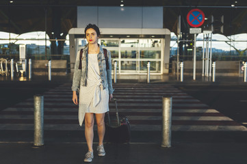 Young traveller woman leaving airport terminal after a flight carrying a backpack and a suitcase
