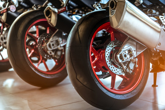 Closeup of new motorbike rear wheel . Big bike parked in showroom of dealership.  Motorcycle exhaust pipes. Iconic motorcycle with sports design. Black tire with unique pattern and red spoked wheels.