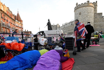 Royal fans are seen sleeping on the pavement having spent the night outside of Windsor Castle