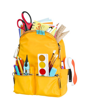 Yellow school backpack with school supplies isolated on white background