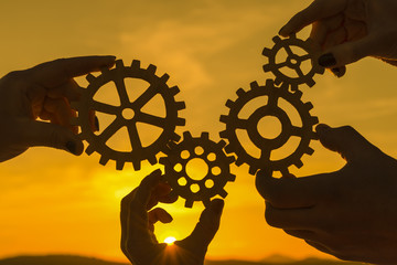 team of people with gears in hands on sunset background. business. interaction.