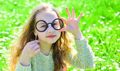Child posing with cardboard eyeglasses for photo session at meadow. Smart and clever concept. Girl on calm face spend leisure outdoors. Girl sits on grass at grassplot, green background.