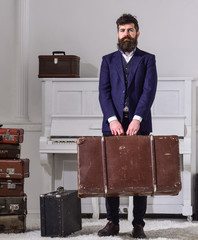 Baggage and travelling concept. Macho stylish on strict face stands and carries big vintage suitcase. Man, traveller with beard and mustache with baggage, luxury white interior background.