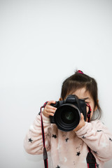 Cute little girl takes picture with digital camera