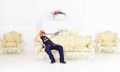 Loader sit on sofa, having rest. Exhausted loader concept. Man with beard, worker in overalls and helmet sits on couch tired, white background. Courier relaxing while moving furniture, relocation.