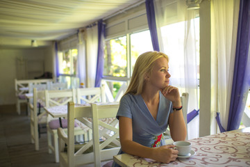 Girl drinks coffee or tea in cafe or restaurant.