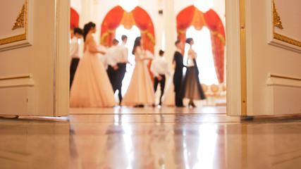 Ladies with cavaliers in vintage costumes dancing waltz