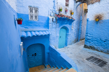 Deurstickers Marokko doors and stairs with blue colored walls in old city in Morocco