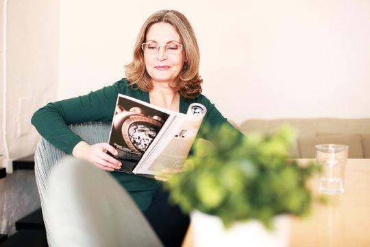 reife Frau beim lesen am Esstisch