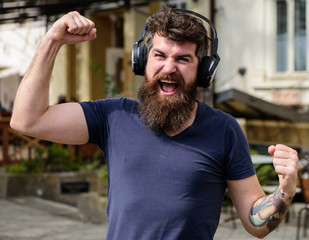 Wireless technologies concept. Hipster with headphones on happy face listening music while walking. Man with long beard and mustache with wireless headphones on head, defocused urban background.