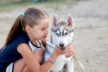 Little cute little girl hugging her dog Husky