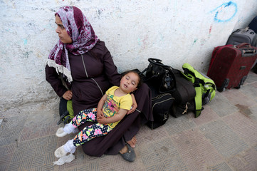 Palestinian girl sleeps as she waits with her mother to travel to Egypt through the Rafah border crossing, in the southern Gaza Strip
