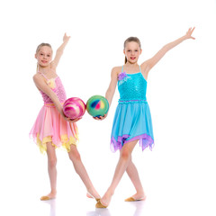 Girls gymnasts perform exercises with the ball.